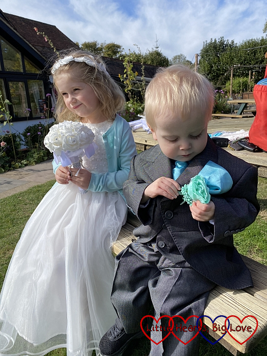 Sophie in her bridesmaid dress and Thomas in his page boy suit sitting on a bench