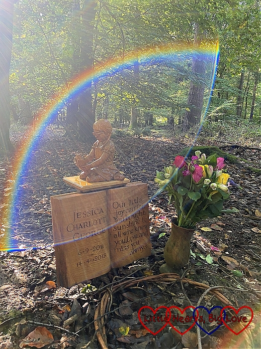 The wooden carving of Jessica at her forever bed surrounded by a rainbow halo