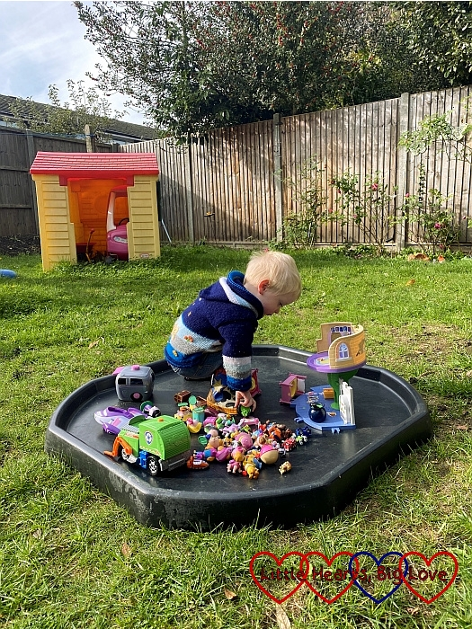 Thomas playing with PAW Patrol and Ben and Holly toys in the tuff tray in the garden