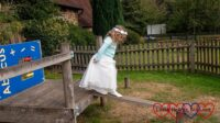 Sophie in her bridesmaid dress walking along a wooden plank
