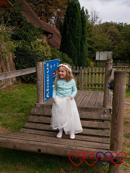 Sophie in her bridesmaid dresses walking over a wobbly bridge in the children's play area