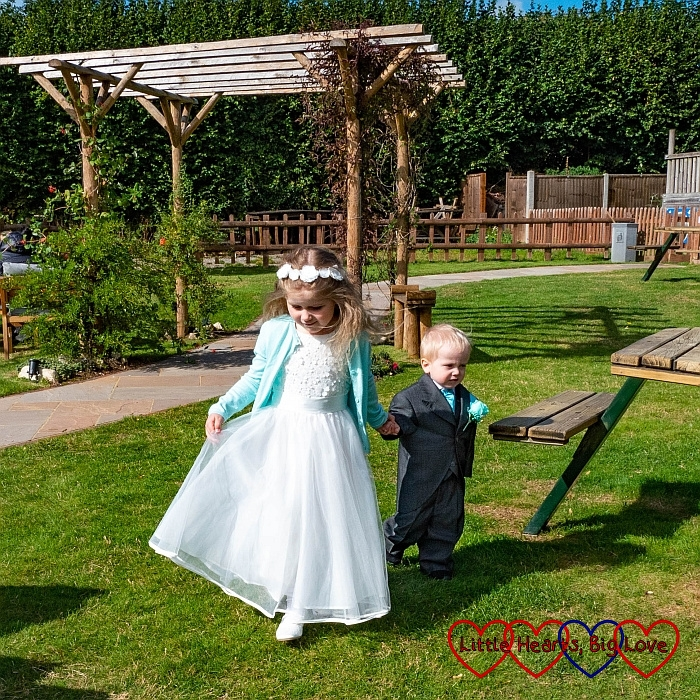 Sophie and Thomas in their wedding outfits, walking through the gardens
