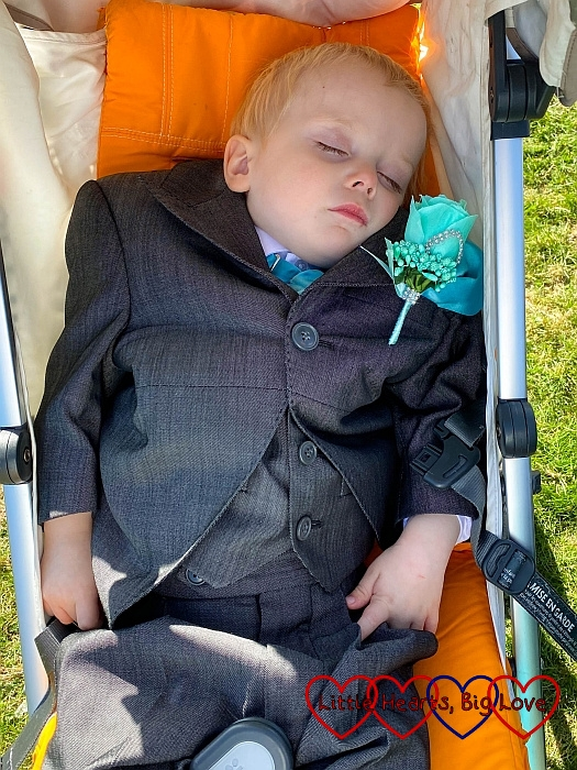 Thomas in his page boy suit asleep in his buggy