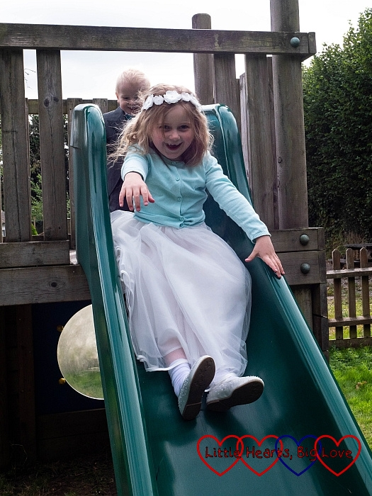 Sophie in her bridesmaid dresses going down a slide with Thomas standing behind her