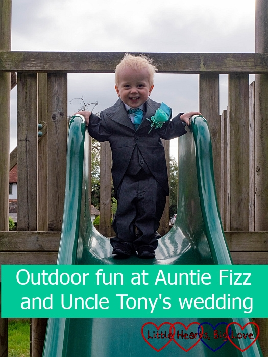 "Thomas wearing his page boy suit standing at the top of the slide with a big grin on his face - ""Outdoor fun at Auntie Fizz and Uncle Tony's wedding"""