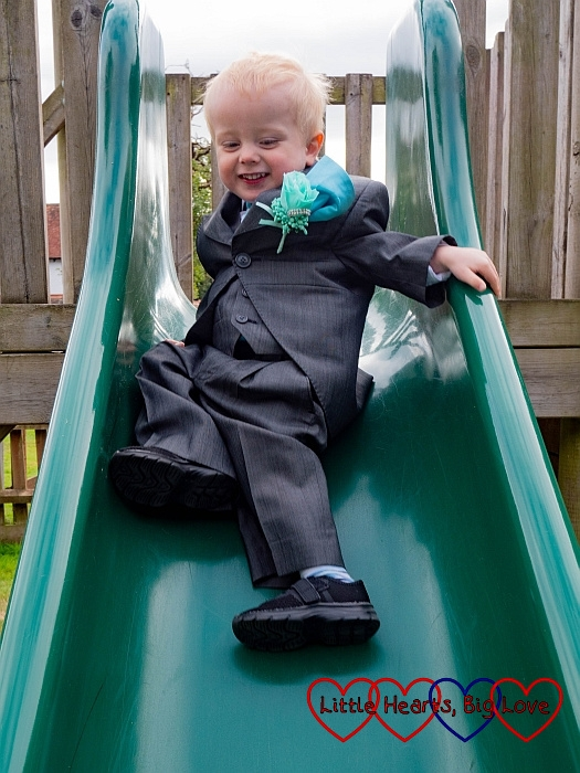 Thomas wearing his page boy suit going down the slide
