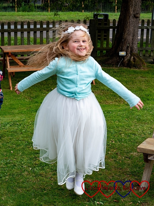 Sophie wearing her bridesmaid dress and jumping into the air