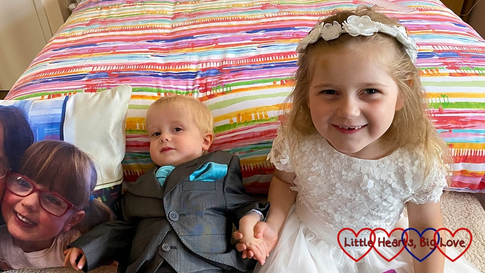 Thomas in his pageboy outfit and Sophie in her bridesmaid dress sitting at the end of Nanny's bed next to Jessica's picture on a cushion