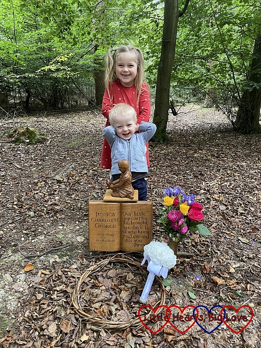 Sophie and Thomas standing behind the carving of Jessica at her forever bed with Jessica's bridesmaid bouquet in front of her memorial