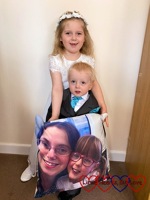 Sophie and Thomas standing and holding the photo cushion with Jessica's photo on