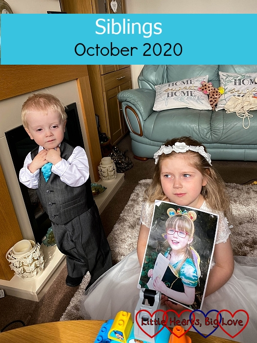 """Thomas standing in his pageboy suit next to Sophie sitting on the floor wearing her bridesmaid dress and holding a picture of Jessica - """"Siblings - October 2020"""""""