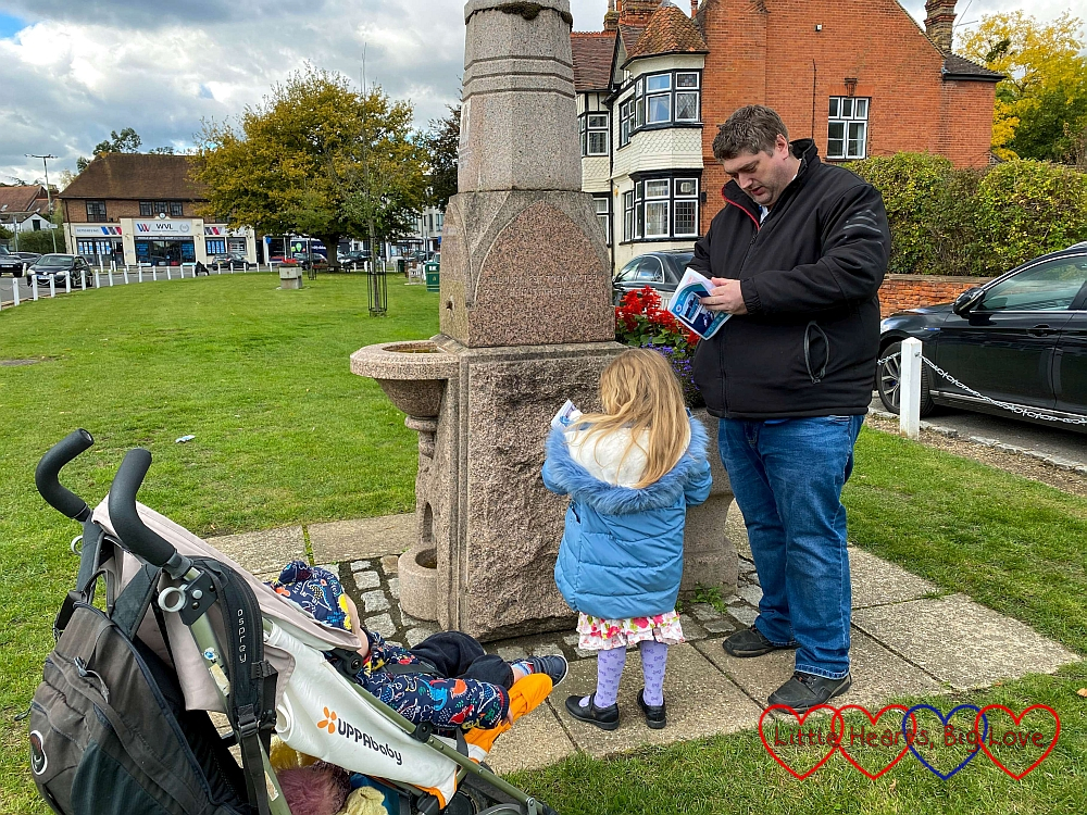 Sophie and Daddy looking at the Victorian drinking fountain in Datchet