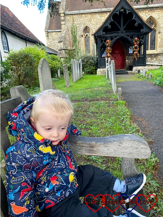 Thomas sitting on a bench outside St Mary's Church in Datchet