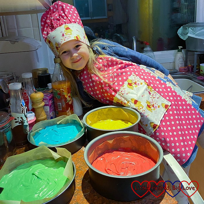Sophie in her new chef's hat and apron with cake tins full of different coloured cake mix