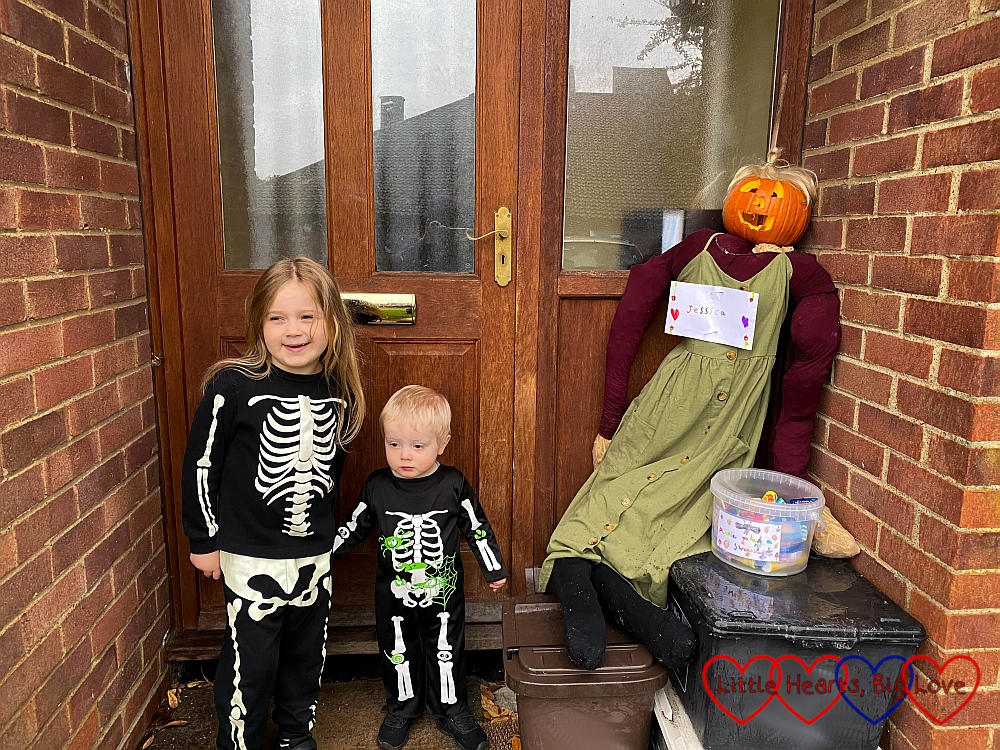 Sophie and Thomas in matching skeleton outfits standing next to the scarecrow Sophie made