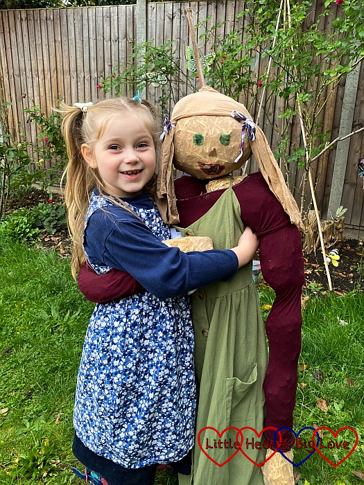 Sophie holding the scarecrow she made
