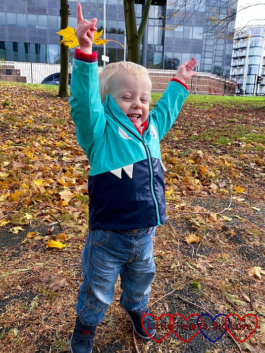 A smiley Thomas throwing leaves in the air