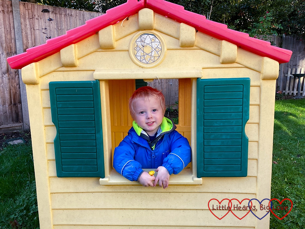 A smiley Thomas looking out of the window of his play house