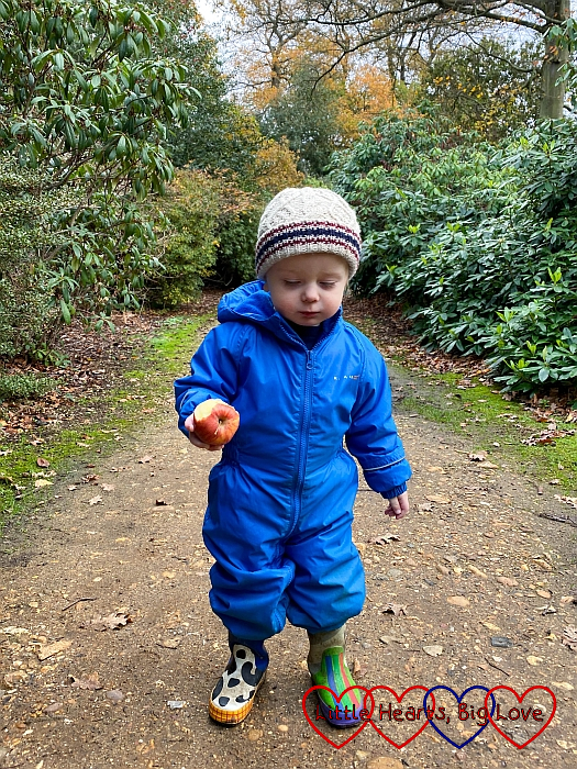 Thomas outside at Langley Park in his puddlesuit and wellies, eating an apple