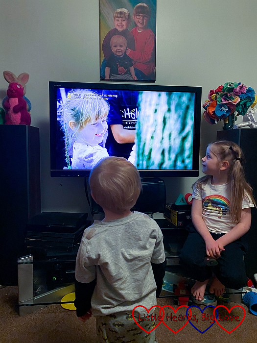 Sophie and Thomas looking at the TV which shows a clip of Sophie pressing her hand on the worry plaque on the tree in Halo's garden