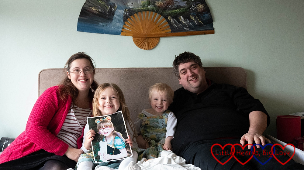 Me, Sophie (holding a picture of Jessica), Thomas and Daddy sitting on a bed together