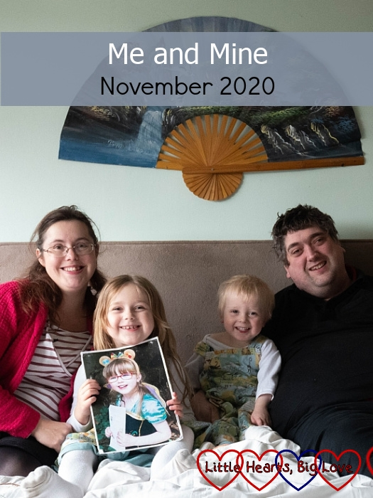 "Me, Sophie (holding a picture of Jessica), Thomas and Daddy sitting on a bed together - ""Me and Mine - November 2020"""