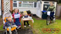 Thomas and Sophie next to two scarecrows in a front garden - one sitting at a table with painted rcks and the other on a bicycle