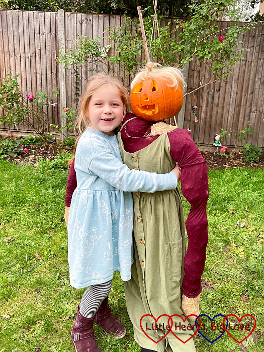 Sophie hugging the scarecrow that she made