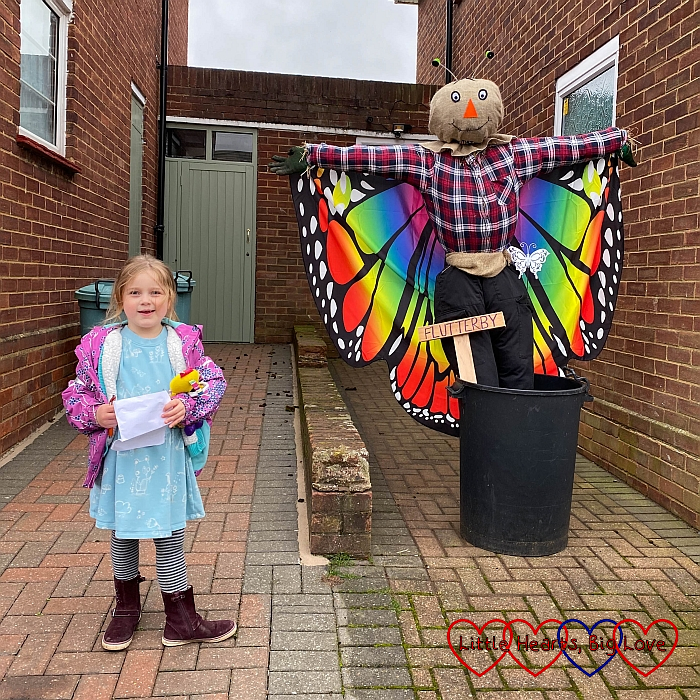 Sophie next to a scarecrow with brightly coloured butterfly wings
