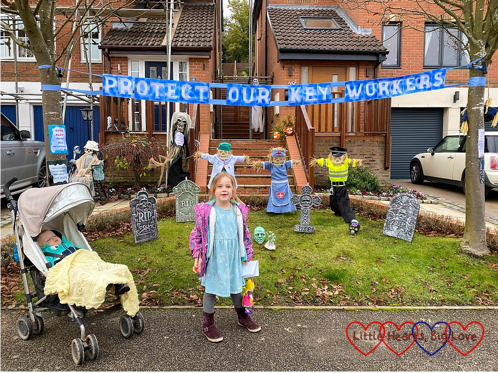 "Sophie standing in front of a display featuring key worker inspired scarecrows and a banner reading ""Protect our key workers"""