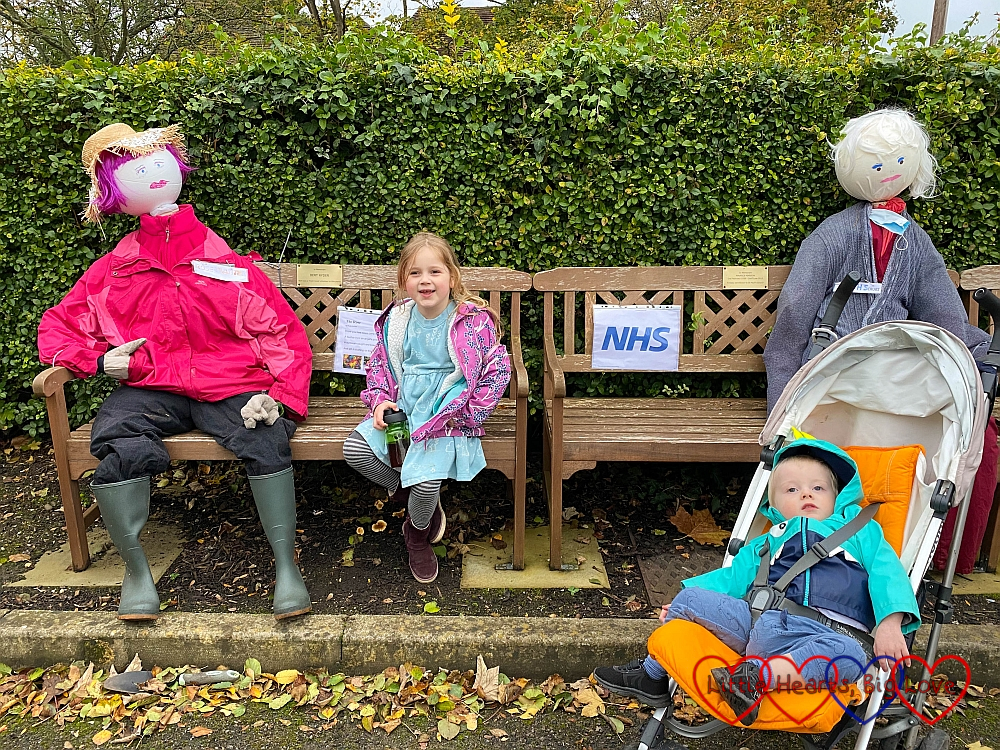 Sophie sitting between two scarecrows on a bench with Thomas in front in his buggy