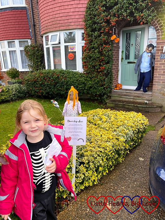 Sophie standing in front of a garden with one scarecrow in the garden looking at a scarecrow by the door