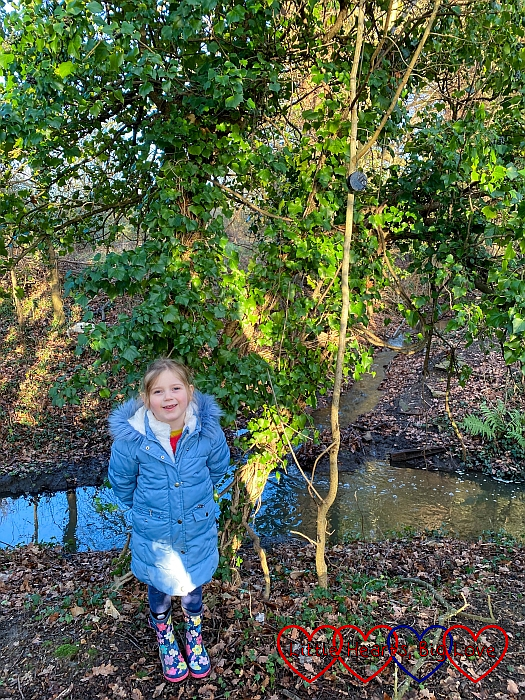 Sophie standing in front of a tree with a stream behind her
