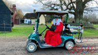 Father Christmas riding a golf buggy covered in tinsel