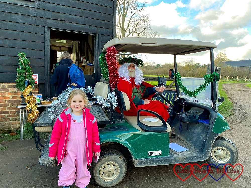 Sophie standing in front of a tinsel-decorated golf buggy with Father Christmas sitting inside