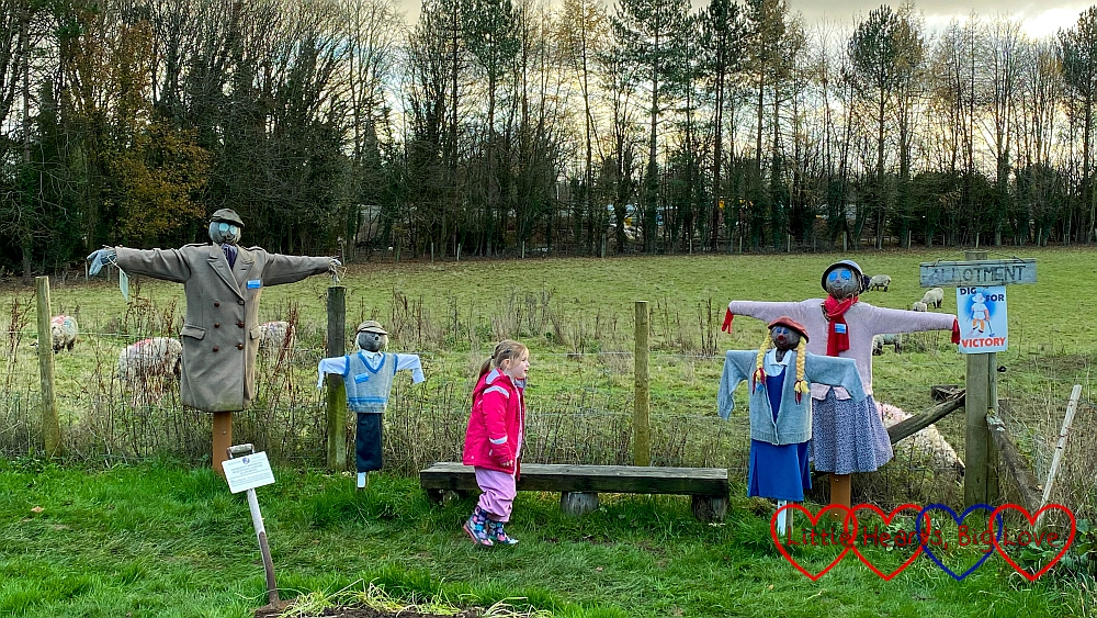 Sophie standing next to a family of scarecrows in the Dig for Victory allotment