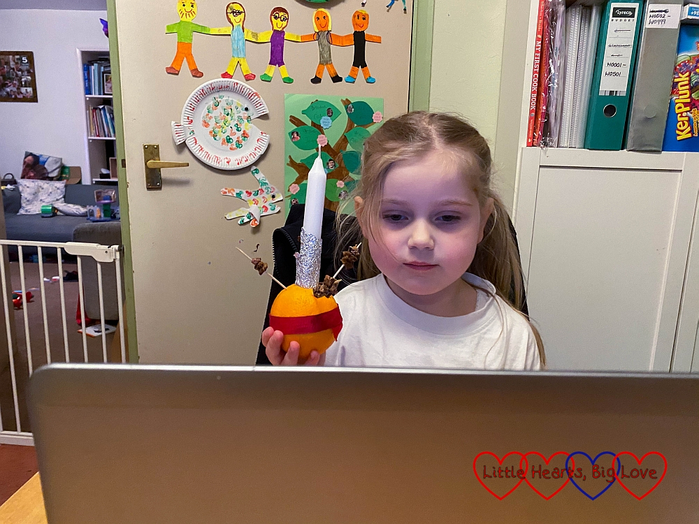 Sophie sitting in front of my laptop, holding up her Christingle