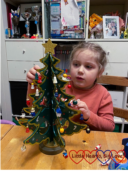 Sophie decorating Jessica's wooden Christmas tree