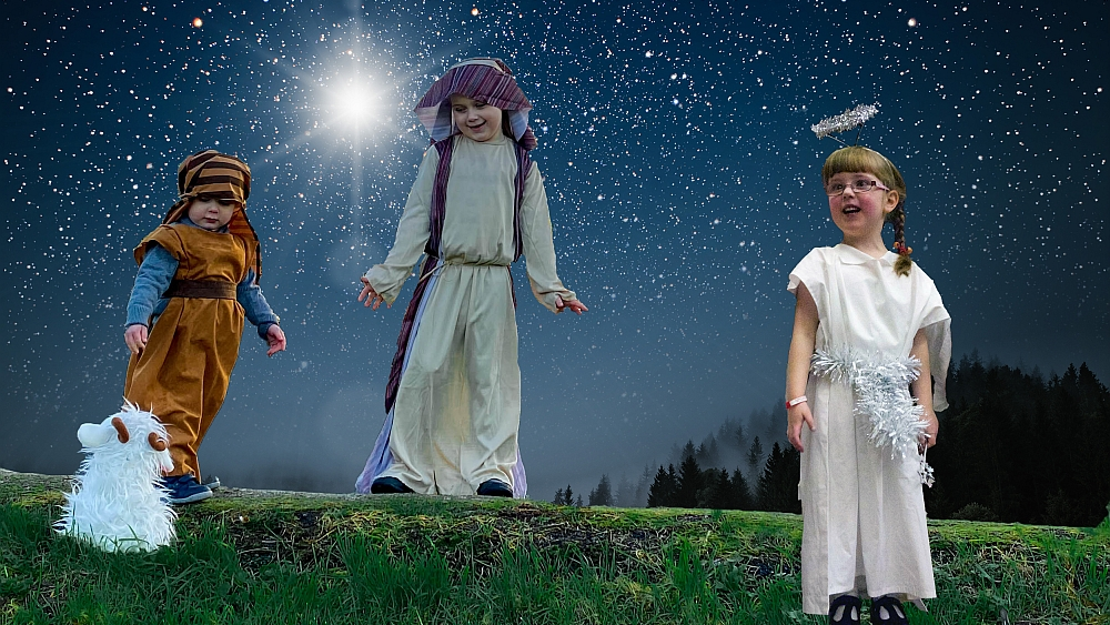 Sophie and Thomas dressed as shepherds with Sophie's toy goat and Jessica dressed as an angel against a starry sky background