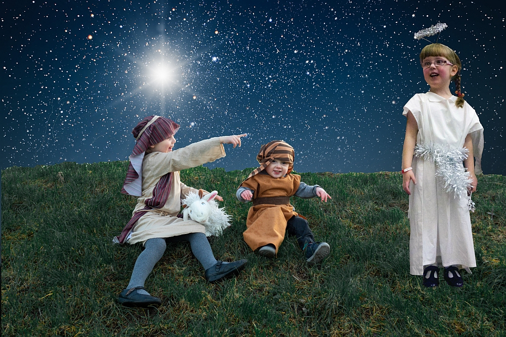 Sophie and Thomas dressed as shepherds pointing at Jessica dressed as an angel against a starry sky background