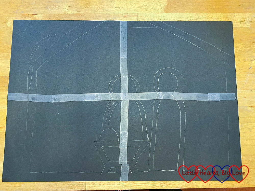 Four A4 pieces of black paper taped together with an outline of a stable with Mary, Joseph and baby Jesus in a manger drawn on it