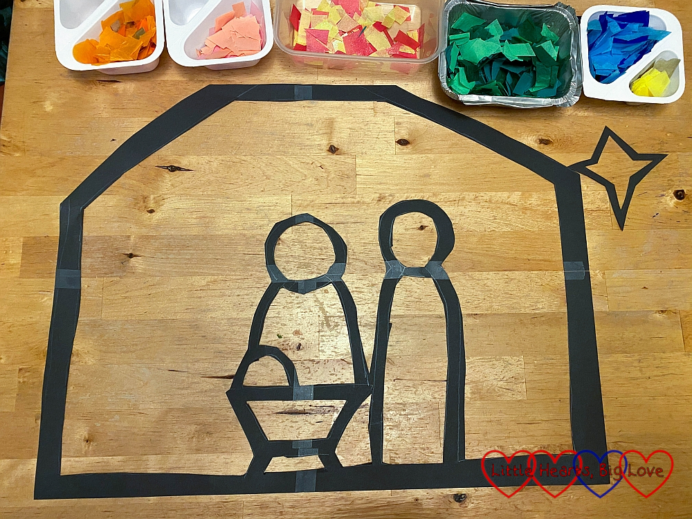 The outine of the stable with Mary, Joseph and baby Jesus in the manger and containers with different colours of tissue paper at the top of the outline