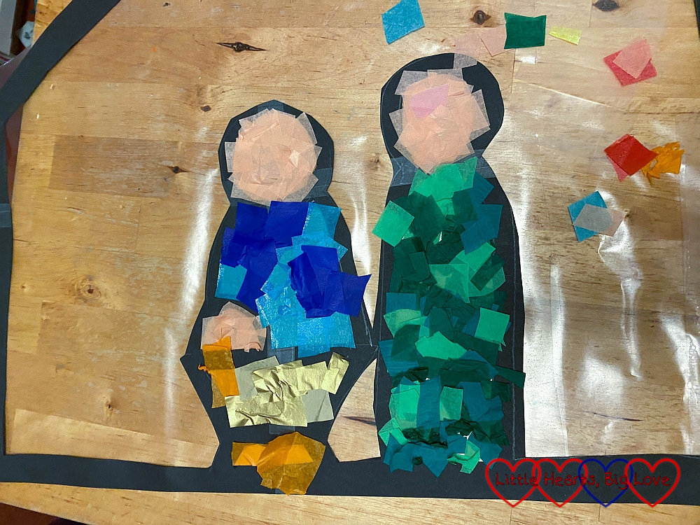 The outlines of Mary, Joseph and baby Jesus in the manger filled in with coloured tissue paper