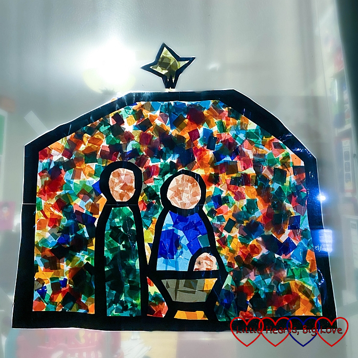 The finished 'stained glass' tissue paper Nativity scene in a window at night with the light shining behind it