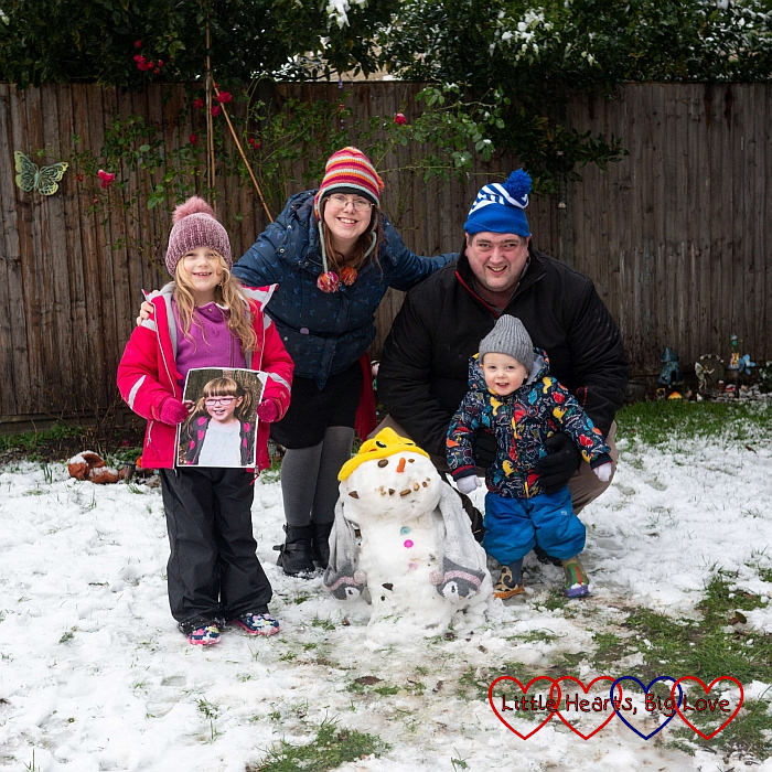 Sophie (holding a photo of Jessica), me, hubby and Thomas out in the garden in the snow with Sophie's snowman in front of us