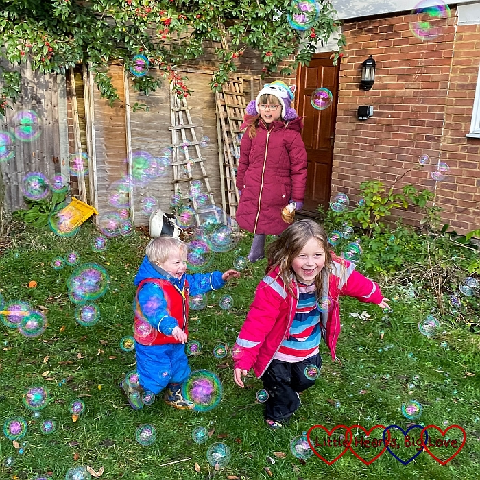 Sophie and Thomas running around chasing bubbles with Jessica stnading in the background