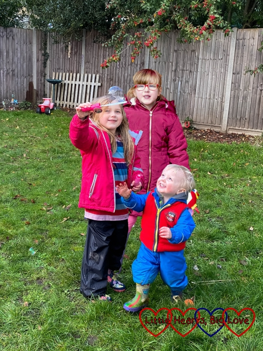 Thomas looking up at Sophie holding a bubble on a bubble wand with Jessica standing behind them