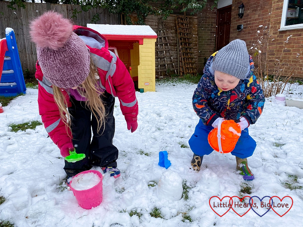 Sophie and Thomas building snow castles with the sand toys