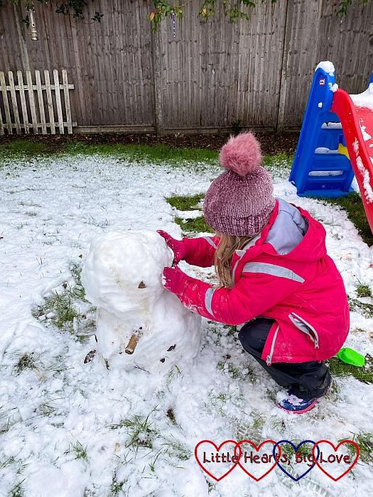 Sophie building a snowman