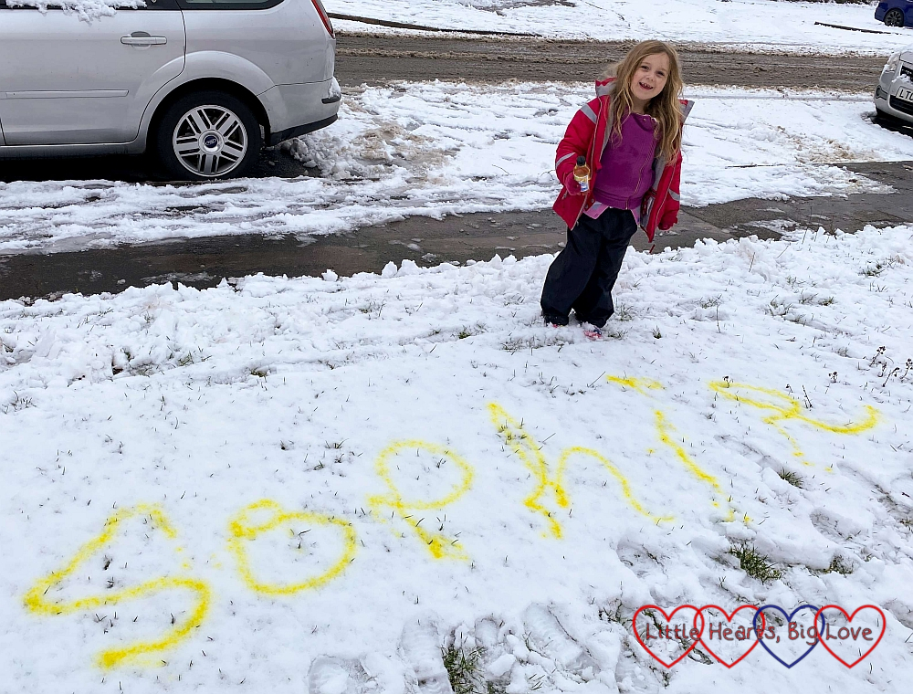 Sophie standing by her name written in the snow